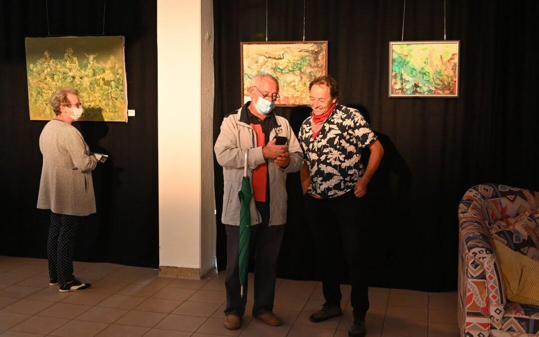 Das Bild zeigt den Kulturkoordinator Holger Wiegandt im Gespräch mit einem Besucher der Vernissage im Kiezladen WaMa.