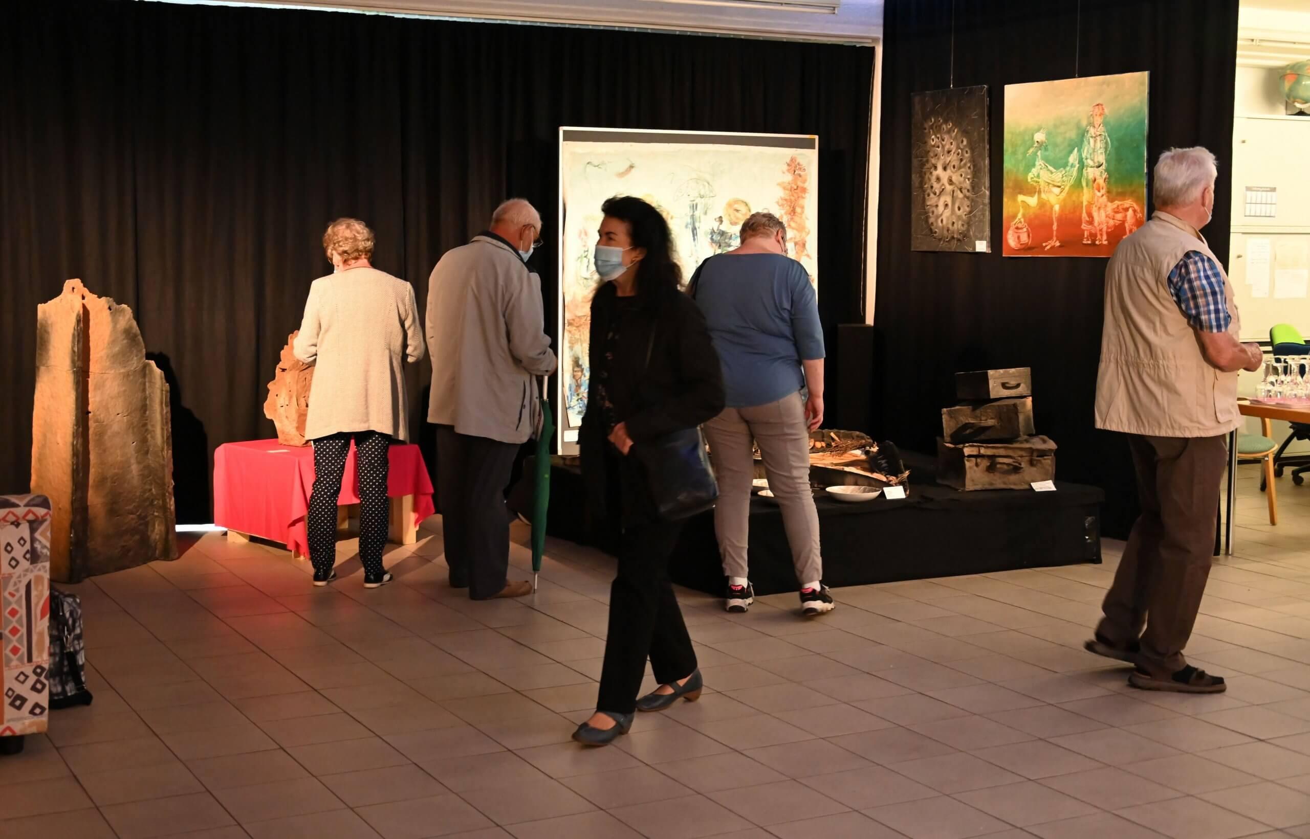 Das Bild zeigt den mit Kunstwerken zur Ausstellung Große Kunst in Altglienicke bestückten Saal im Kiezladen der Möglichkeiten WaMa.