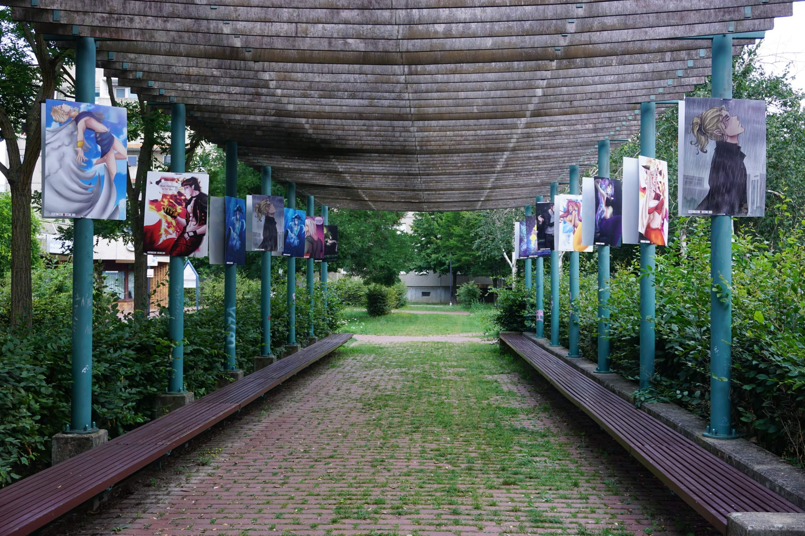 Das Bild zeigt die Pergola im Kosmosviertel, an deren Pfeilern zweiseitig jeweils zwei Replikate der Mangas im Großformat angebracht wurden.