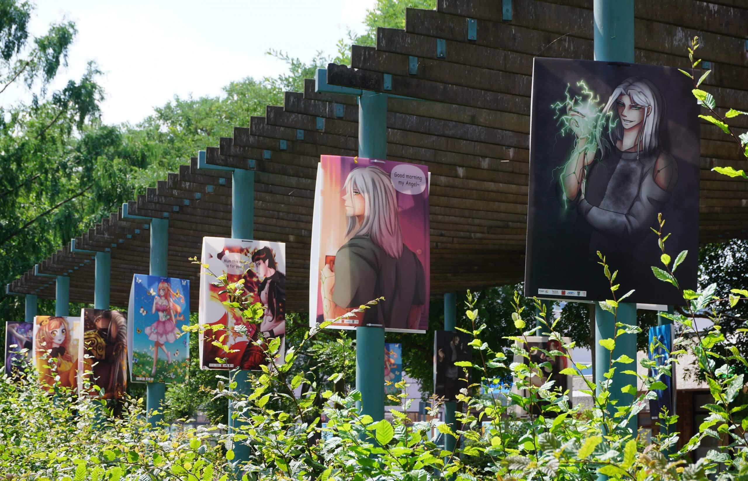Das Bild zeigt den Blick von Außen auf eine Reihe von Mangas, die in der Pergola angebracht sind.